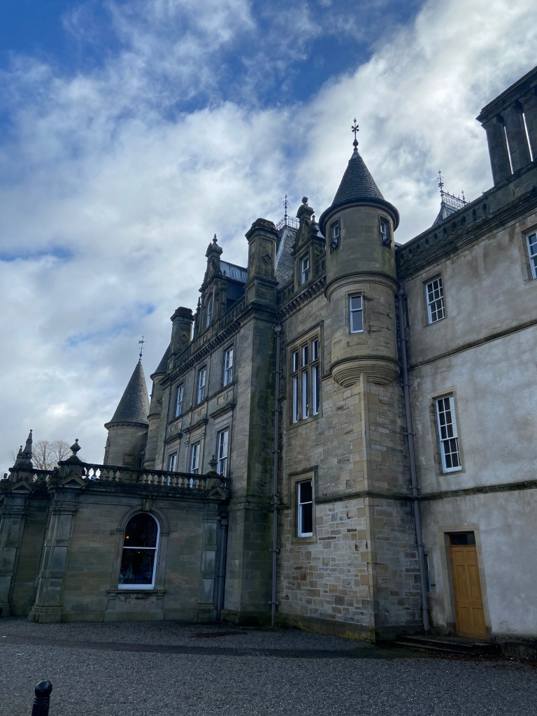 A picture of a large, old country house with turrets on the roof.
