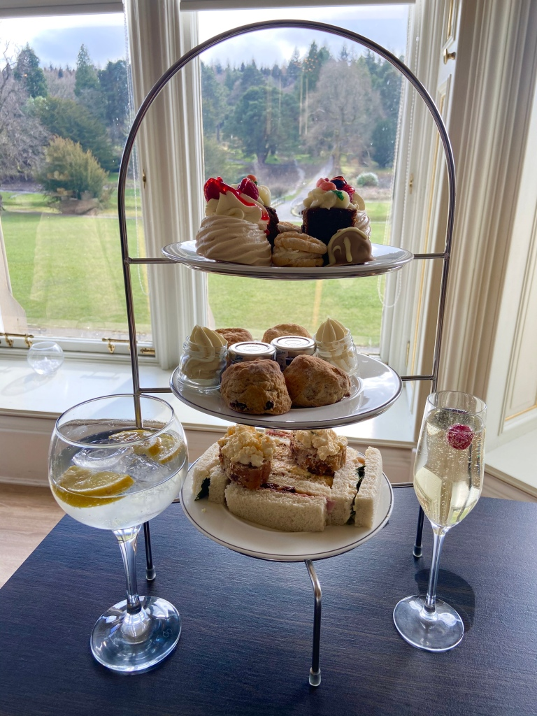 A stand with afternoon tea components on it: sandwiches, scones and cakes. Next to it is a large bowl glass of gin and tonic and a champagne flute.
