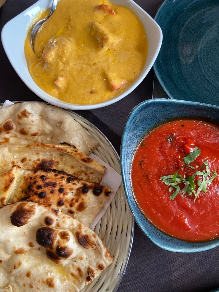 Three plates. One with naan bread, one with a yellow curry and the ither with a red curry.