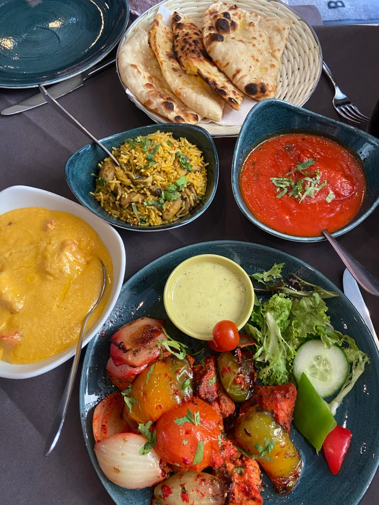 A selection of indian dishes - naan bread, rice, two curries and a place of grilled chicken and vegetables.