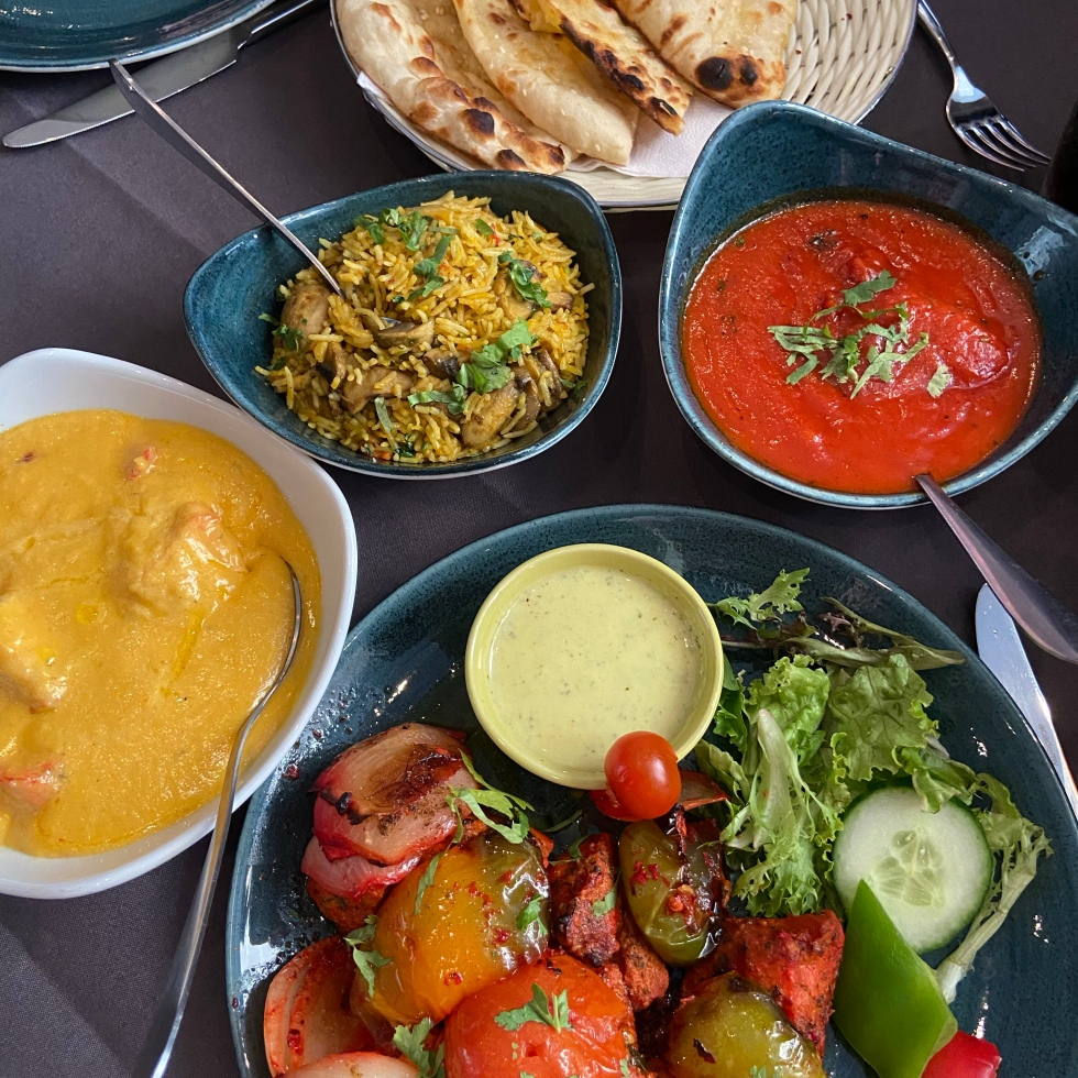 A selection of dishes on a grey table cloth. The dishes are all bright colours.
