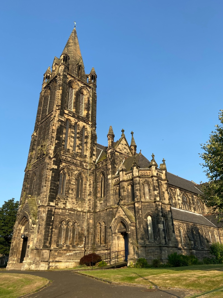 The sky is blue, and the picture is of a very large gothic styled church surrounded by trees.