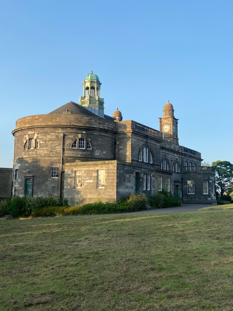 The sky is blue and the grey stone building is a large rectangle, rounded at one end. There is a tower with a green copper roof, and another separate clock tower.