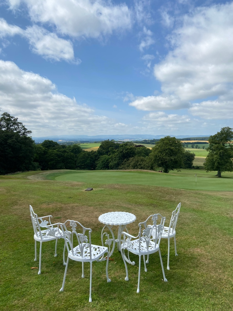 White metal garden furniture on the grass with views over Perth.