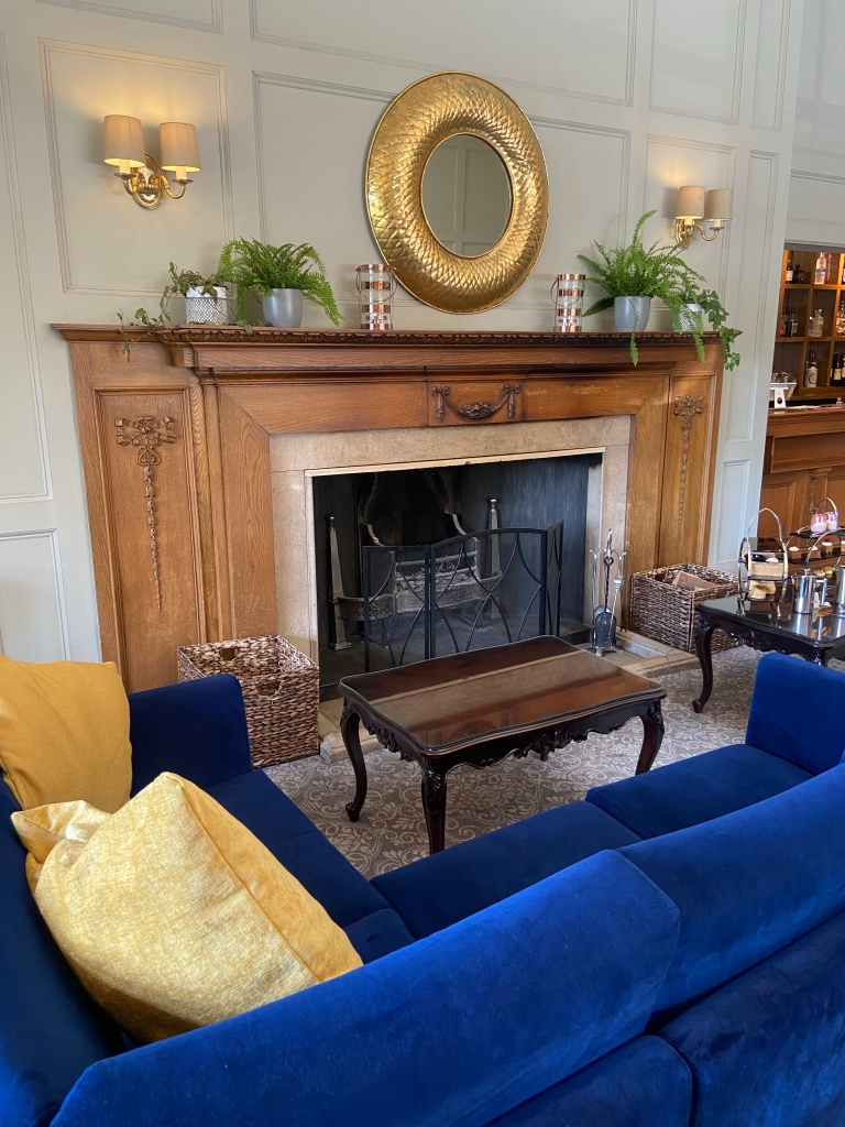 A royal blue velvet L-shaped couch with yellow cushions which sits in front of a large wooden fire place, with a gold mirror above.
