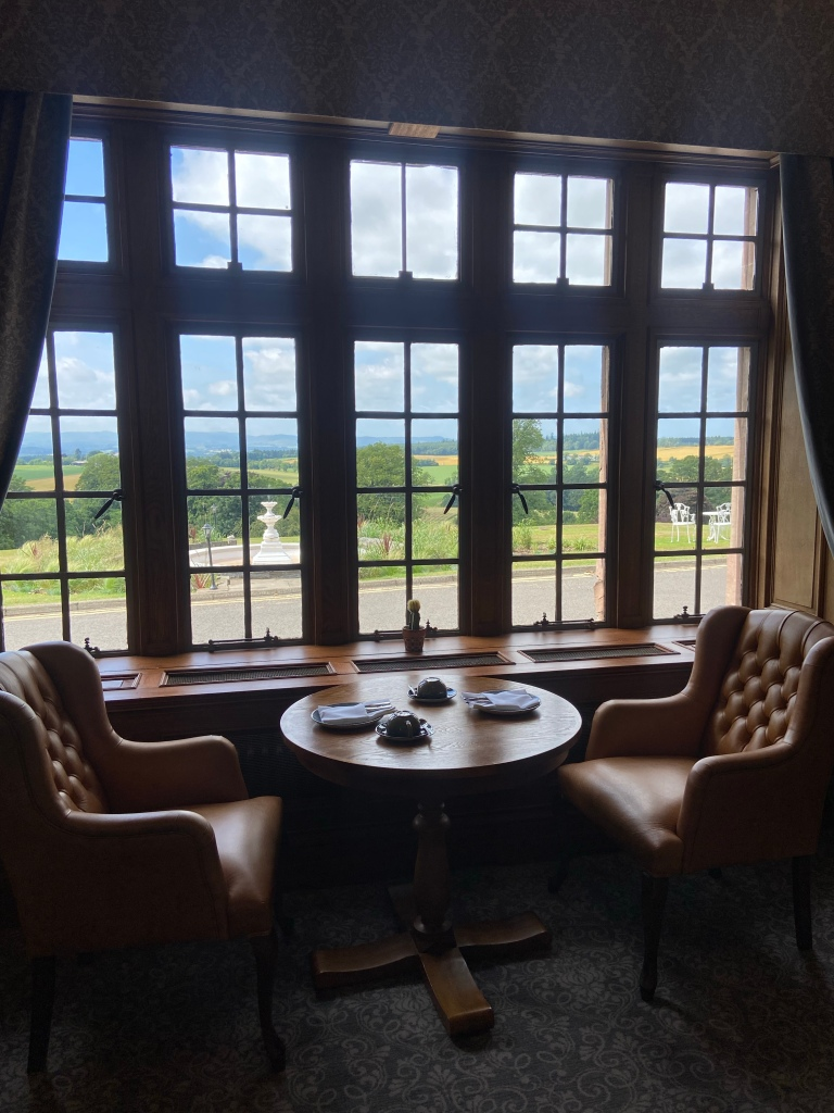 A table for two with twonkeather chairs. The table is next to a large window with views of the golf course.