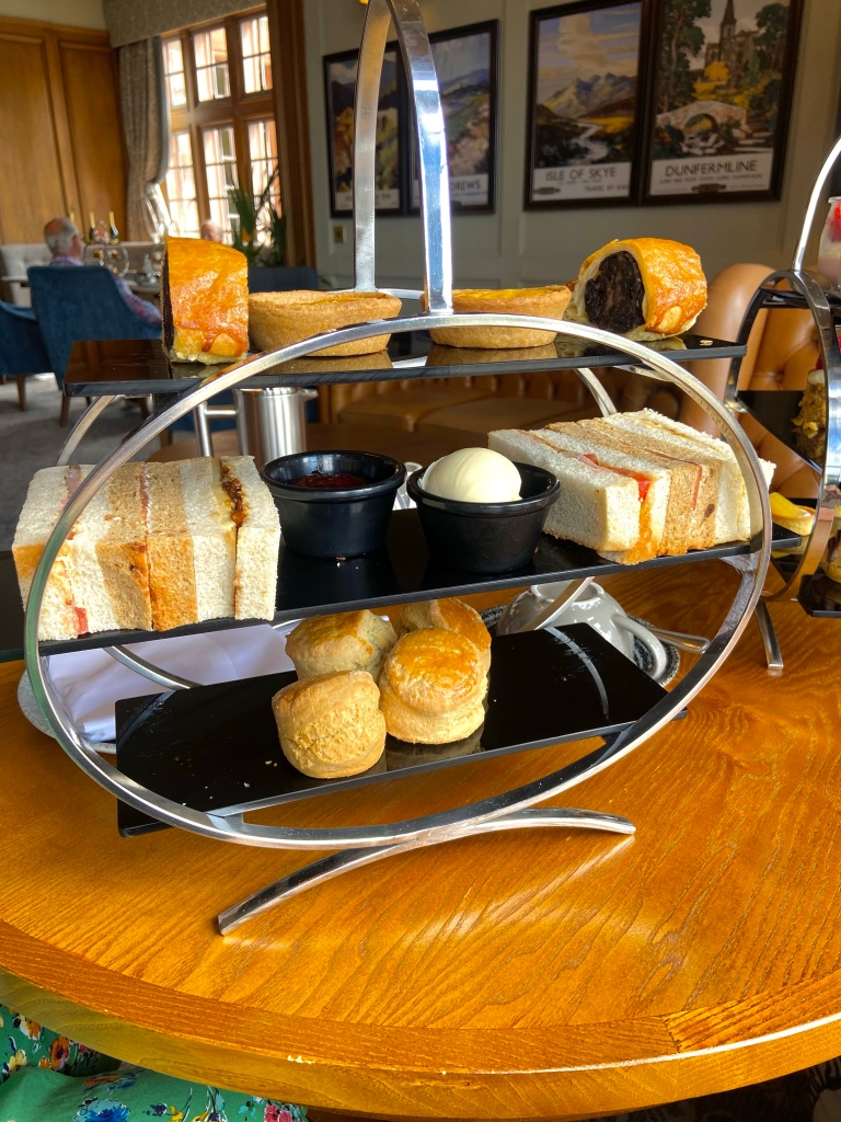 A silver metal stand with sandwiches, pastries and scones on it.