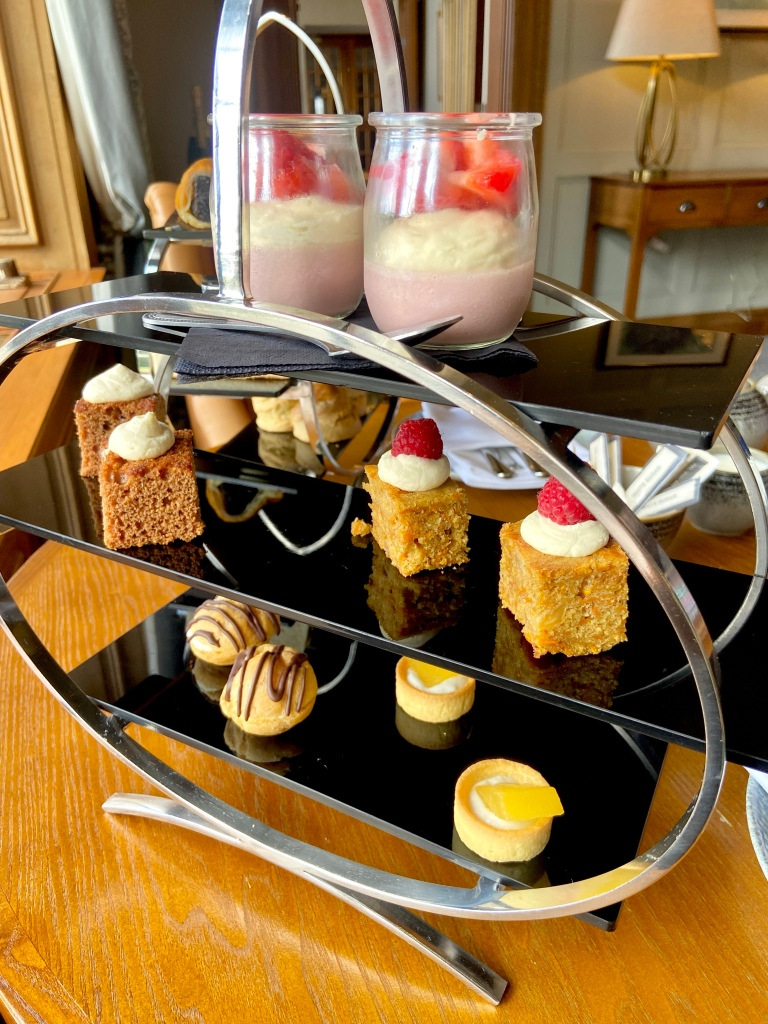 A stand with profiteroles, mini fruit tarts, cakes abd strawberry mousse.
